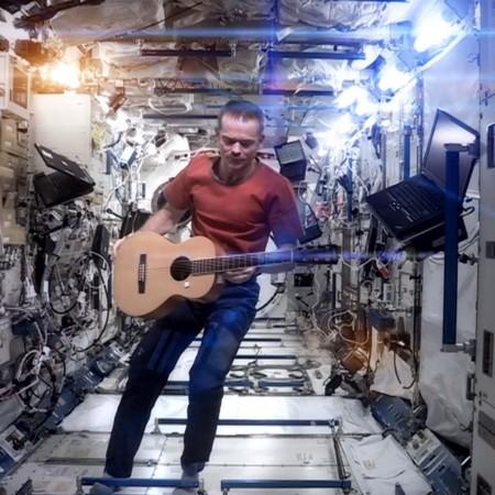 Man i rymdfarkost spelar gitarr.