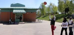 Elever spelar basket på skolgård.