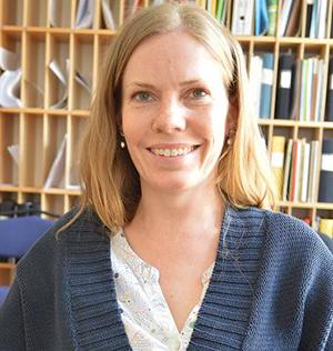 Lisa Clausson framför bokhyllor.