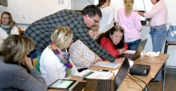Pedagoger sitter vid bord med sina datorer och en man lutar sig fram för att hjälpa.