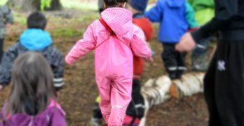 Barn i regnkläder balanserar på stockar.