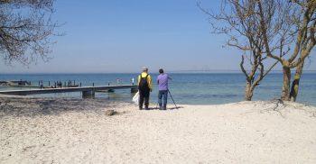 Två personer vid strandlinjen.