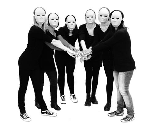 Sex personer med vita masker håller in händerna i mitten.
