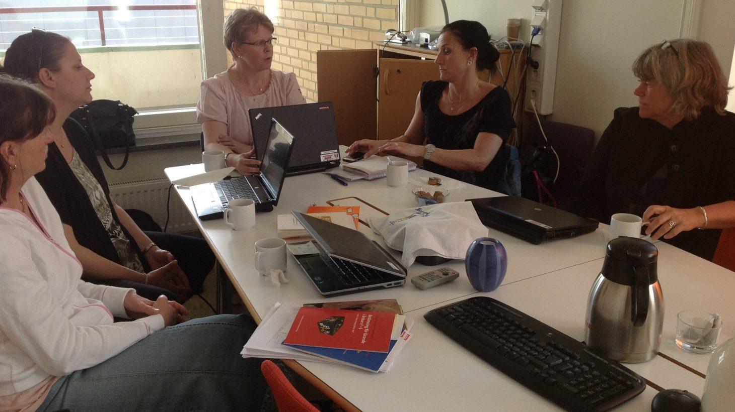 Fem personer sitter runt ett bord fyllt av datorer.