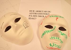 Två masker ligger på papper med fråga om hur du arbetar antirasistiskt på din skola.