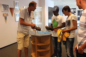 Man visar upp fotbollssko för tre elever.