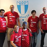 Sex personer iförda röda t-shirtar med texten: Ge rasismen rött kort, håller om varandra