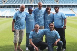 Sju män klädda i MFF-tröja håller om varandra inne på stadion.