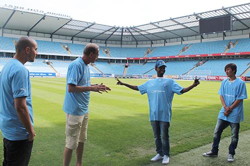 Två män och två pojkar samtalar vid sidlinjen inne på stadion.