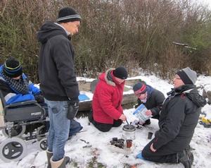 Fem personer sitter och står runt eld i snö.