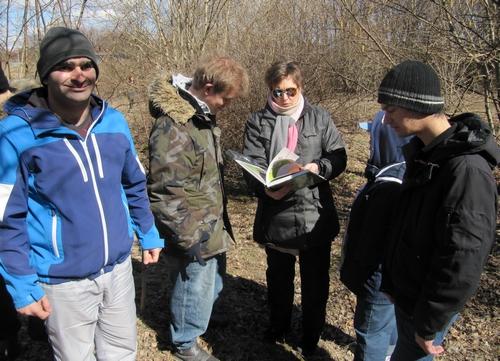 Kvinna bläddrar i bok samtidigt som fyra elever tittar i boken.