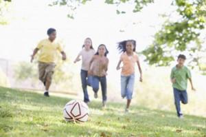 Fem barn springer på grön äng.
