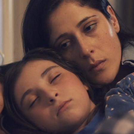 Kvinna omfamnar sovande barn.