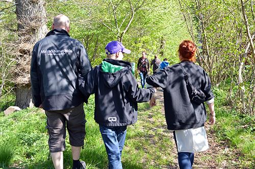 Tre personer håller varandra i handen medan de går bortåt.