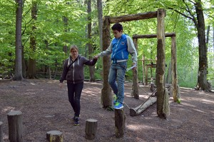 Pojke håller hand medan han tar sig igenom naturhinderbana.