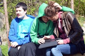 Tre personer sitter på en bänk, två av dem tittar ner i en läsplatta.