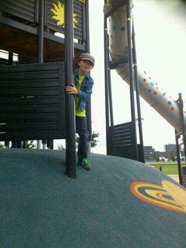 Pojke leker på sollekplatsen.