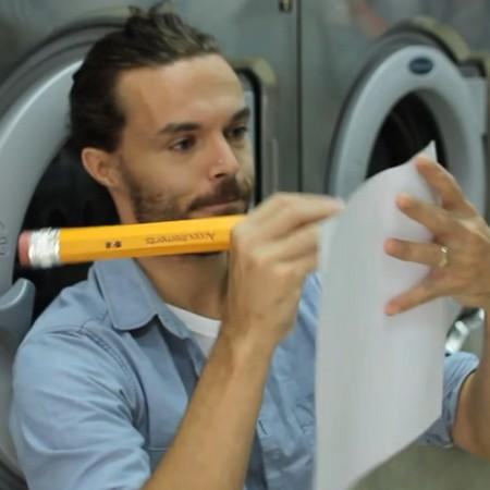 Man skriver med jättestor blyertspenna på papper.