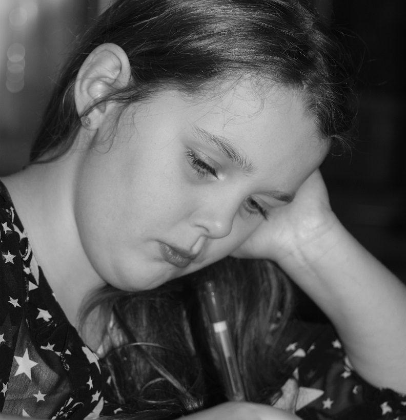 Flicka lutar huvudet i handen medan hon skriver.