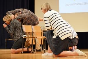 Fyra personer sitter på knä på scen under pjäs.