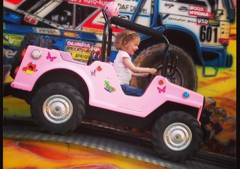 Flicka kör bil i karusell.