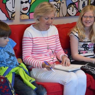 Kvinna läser för två elever.