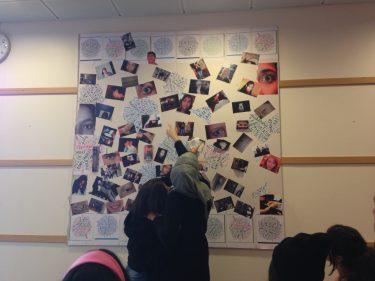Elever titta rpå foton uppsatta på vägg.
