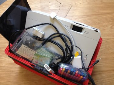 Projektor och pennor ligger i röd kundkorg.