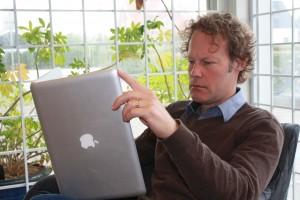 Lars Berggren läser i bibliotek på en upp och ner vänd dator.