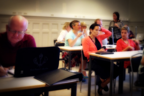 Elever sitter vid bord i klassrum.