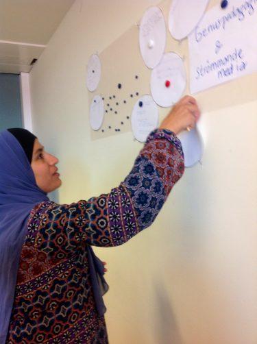 Kvinna sätter upp pratbubbla på vägg.