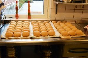 Brödbullar i rad på plåtar.