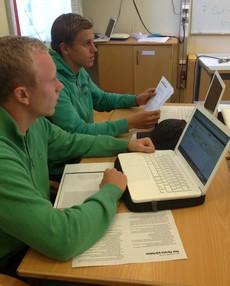 Två elever sitter med varsin bärbar dator.