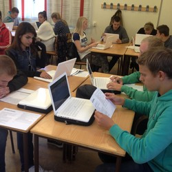 Elever sitter vid bord med varsin dator.