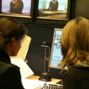 Två kvinnor sitter framför dataskärm.
