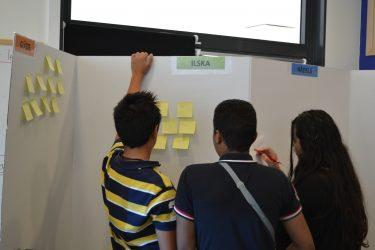 Elever tittar på post it-lappar uppsatta på vikbar vägg.