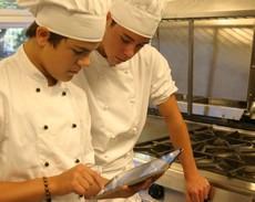 Två elever i kockkläder tittar på ipad.