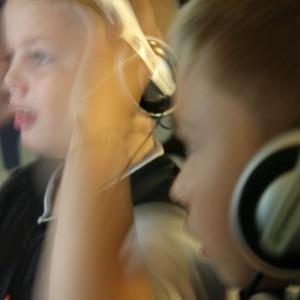 Två barn med hörlurar.
