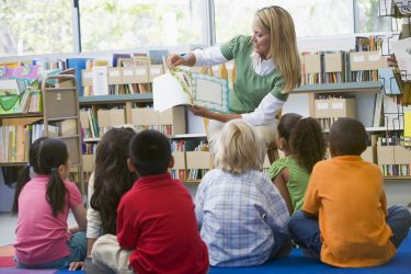 Förskollärare läser för barn som sitter framför henne.