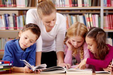 Kvinna lutar sig över tre elever som läser.