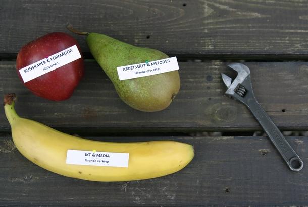 Äpple, päron och banan bredvid en skiftnyckel.