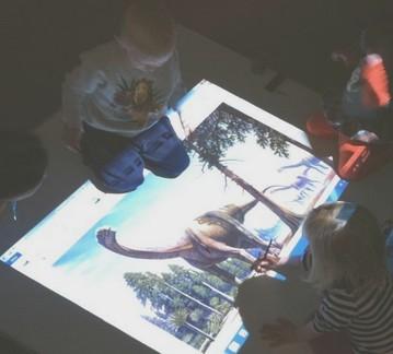 Barn tittar på projicerad bild av dinosaurie.