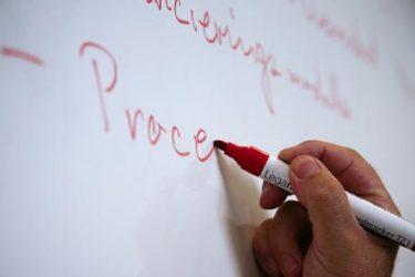 Han skriver med röd penna på whiteboard.