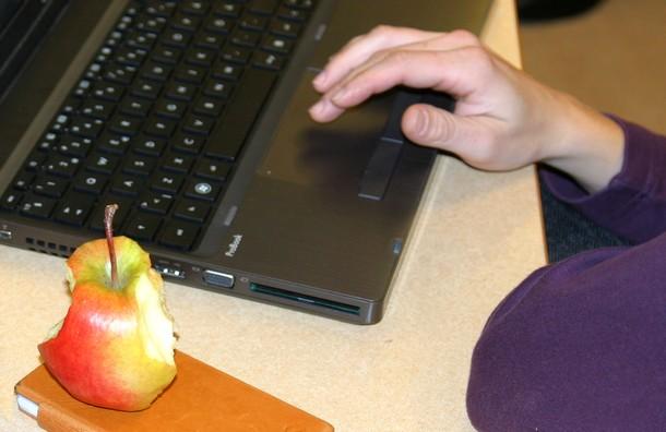 Halvätet äpple ligger vid tangentbord.