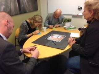 Människor sitter runt ett bord och skriver.