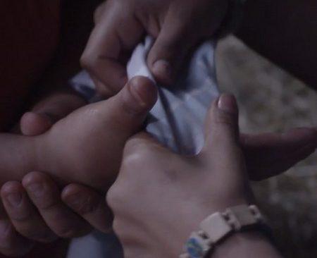 Händer håller i tygstycke.