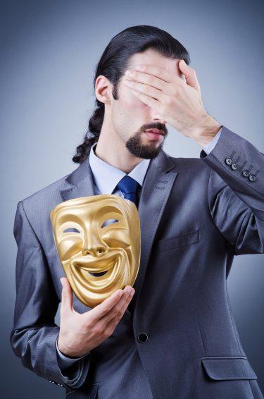 Man i kostym håller hand för ögonen och håller en guldig mask i handen.