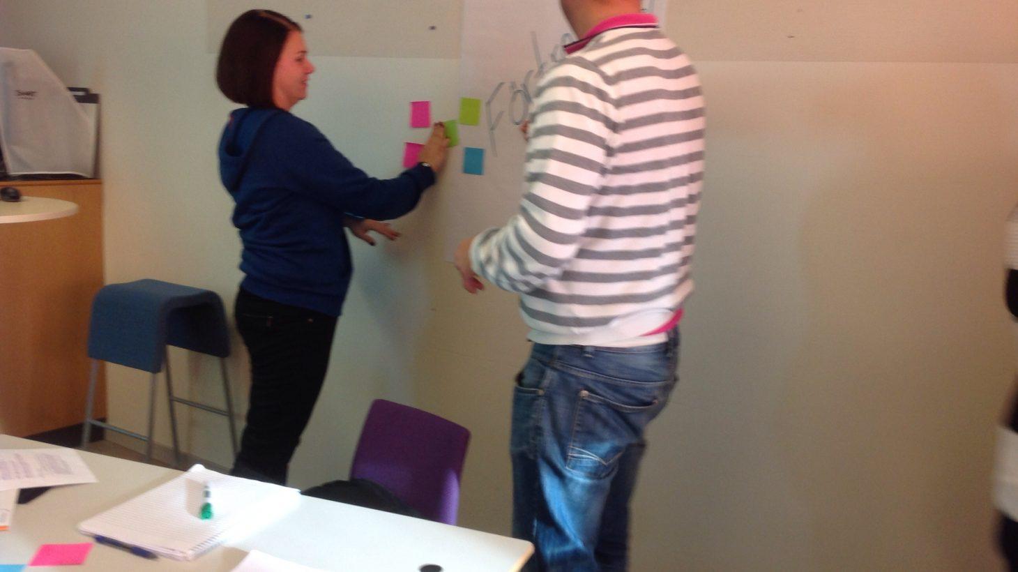 Kvinna och man sätter upp post-itlappar på vägg.