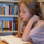 Flicka läser uppslagen bok.