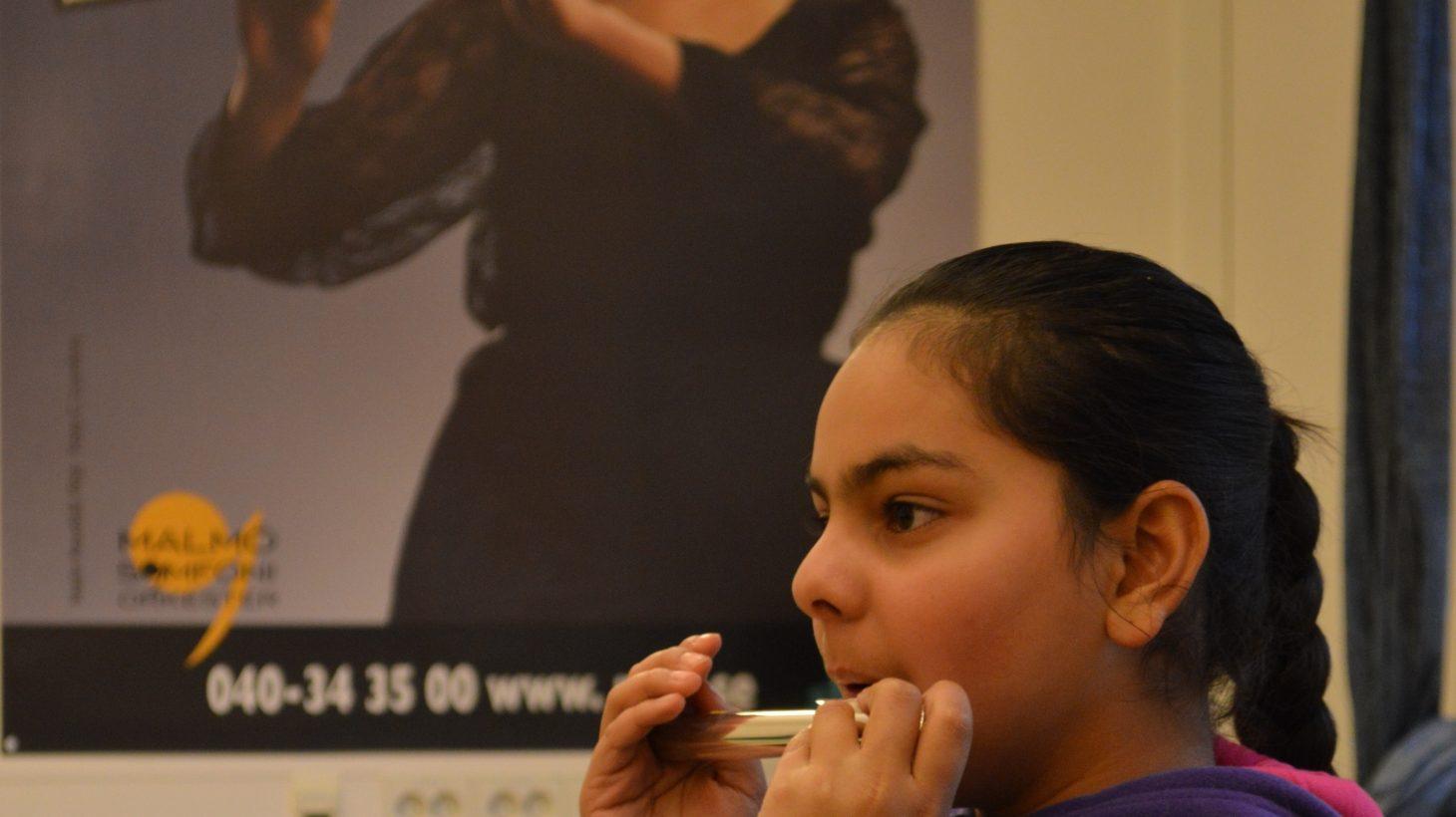 Flicka spelar flöjt i bakgrunden kvinna som spelar tvärflöjt.